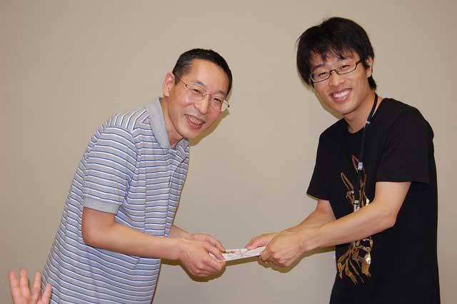山岸団長からお祝いを受け取る飯島氏(左)