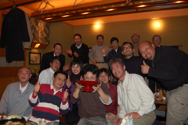 なぜか、祝杯を湯浅氏が!? 後列中央で見守る谷氏、そして団員面々